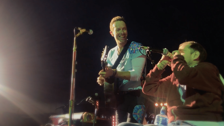 Chris Martin on stage with disabled fan Rob.