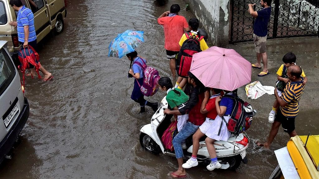 School students cross a waterlogged street after heavy rains in New Delhi on Thursday.