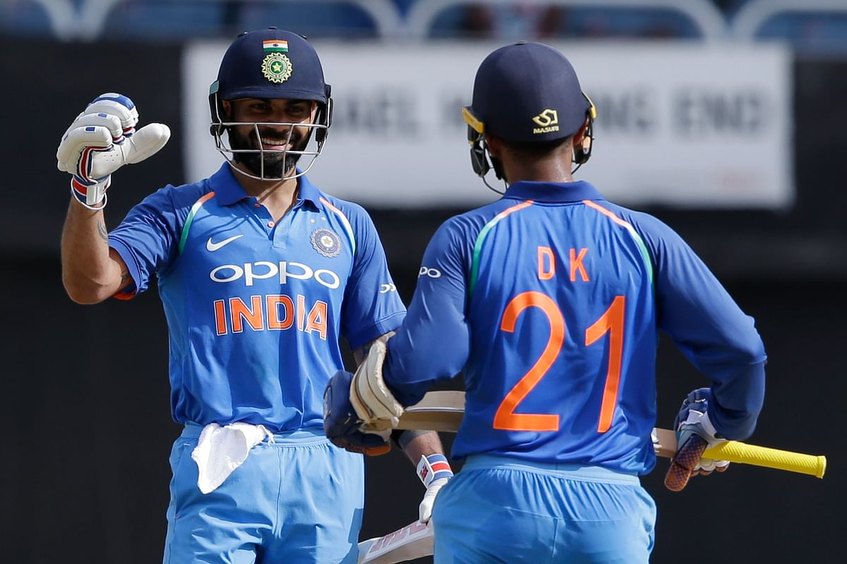 India's captain Virat Kohli, left, greets Dinesh Karthik after he scored a half century against West Indies during the fifth ODI at the Sabina Park.
