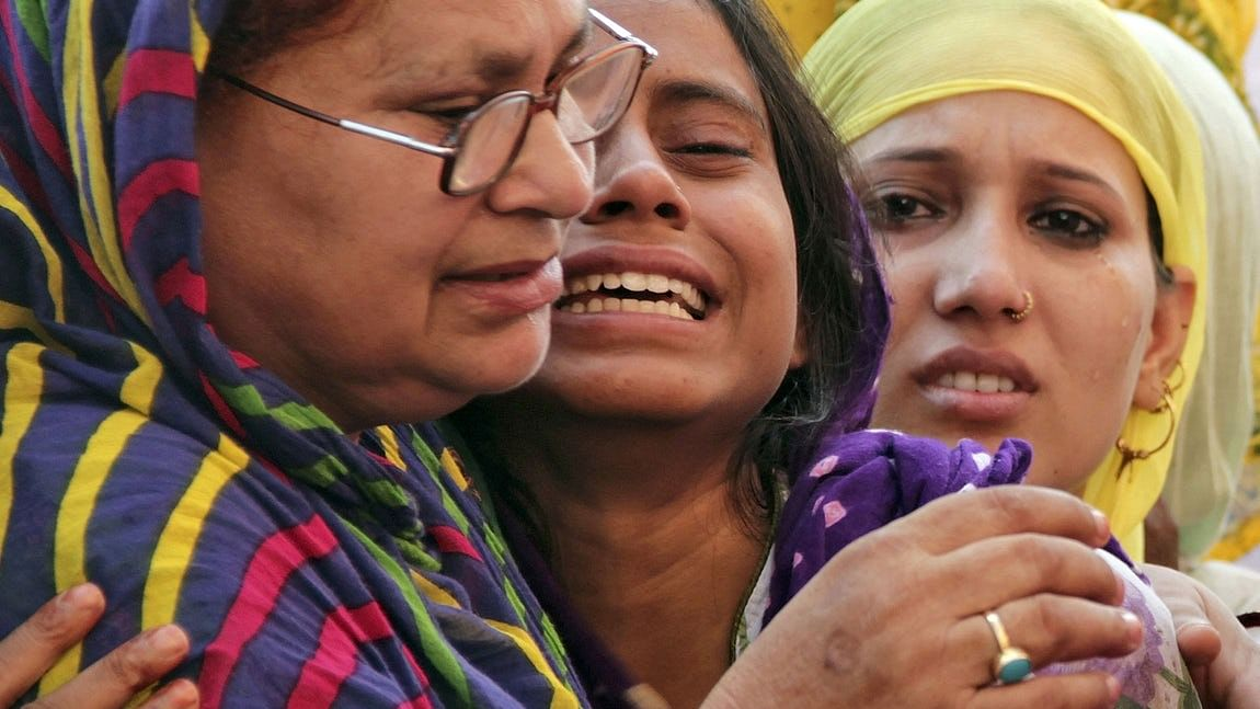 Akhlaq's 18-year-old daughter Shaista (centre) being consoled after her father Akhlaq's death.