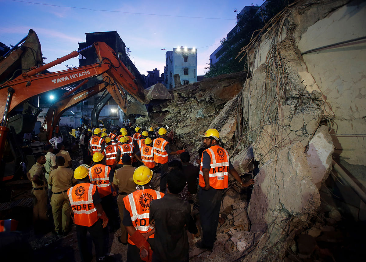 Rescue crew members search for survivors at the site of a collapsed residential building in Mumbai on 28 September 2013.