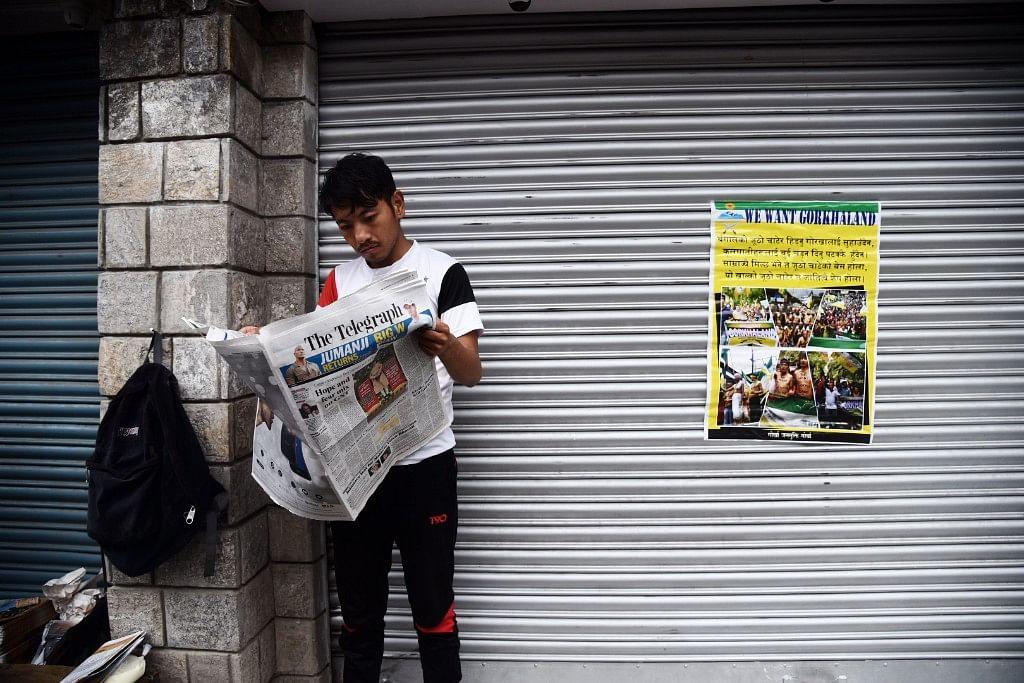 A lone man reads a newspaper.