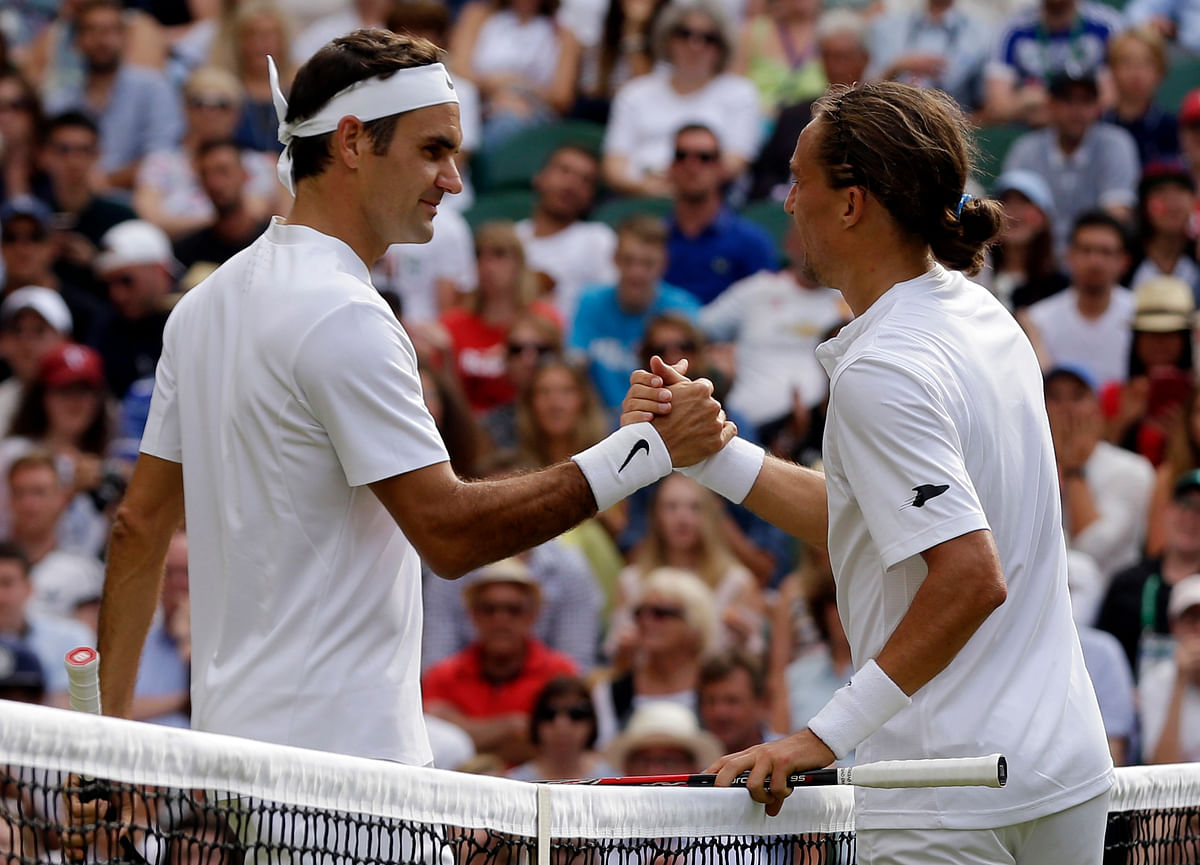 Switzerland's Roger Federer, left, shakes hands with Ukraine's Alexandr Dolgopolov after winning their Men's Singles Match on day two at the Wimbledon