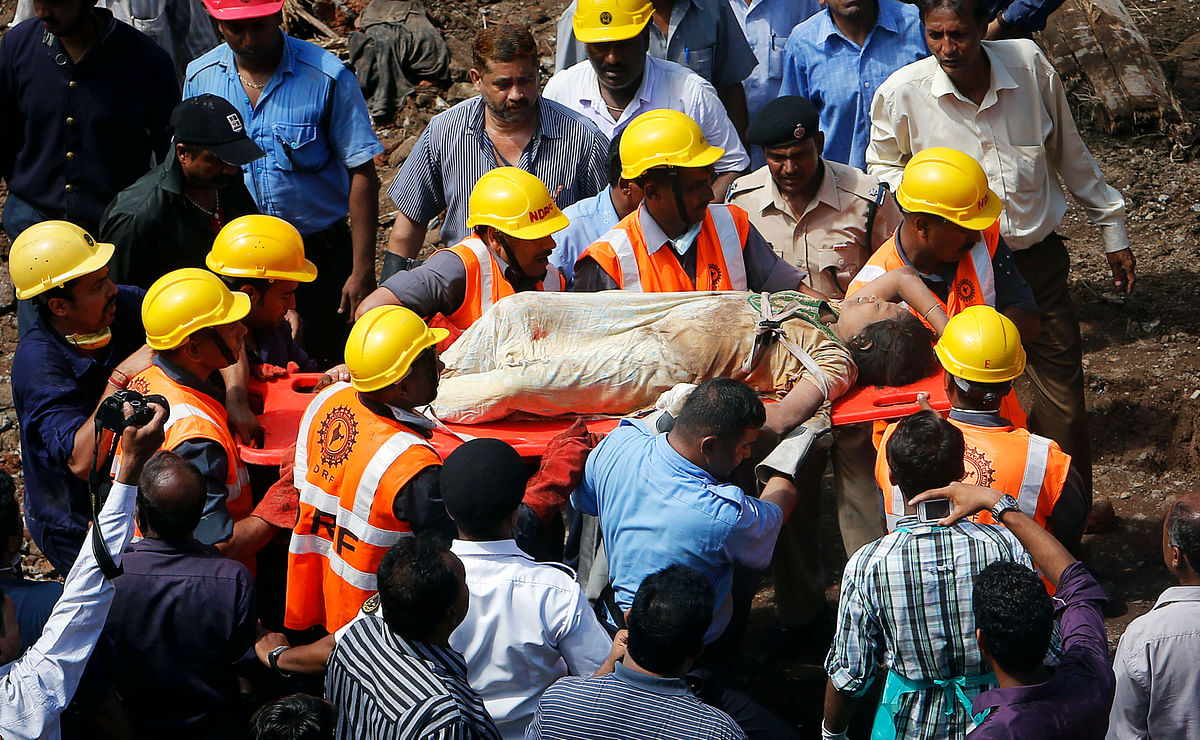 Rescue workers use a stretcher to carry a woman who was rescued from the rubble at the site of a collapsed residential building in Mumbai on 27 September  2013.