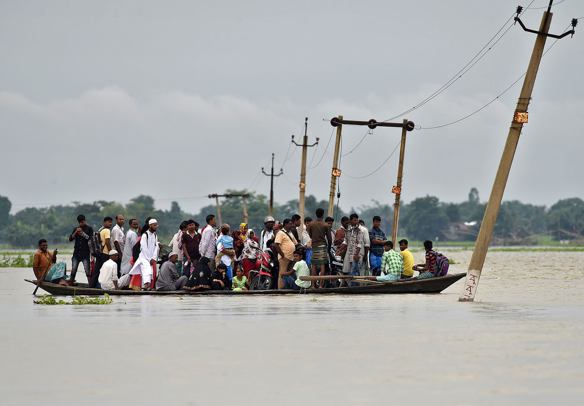 Villagers use a boat to cross a flooded road at Asigarh village in Morigaon district in the northeastern state of Assam. (Photo: Reuters)