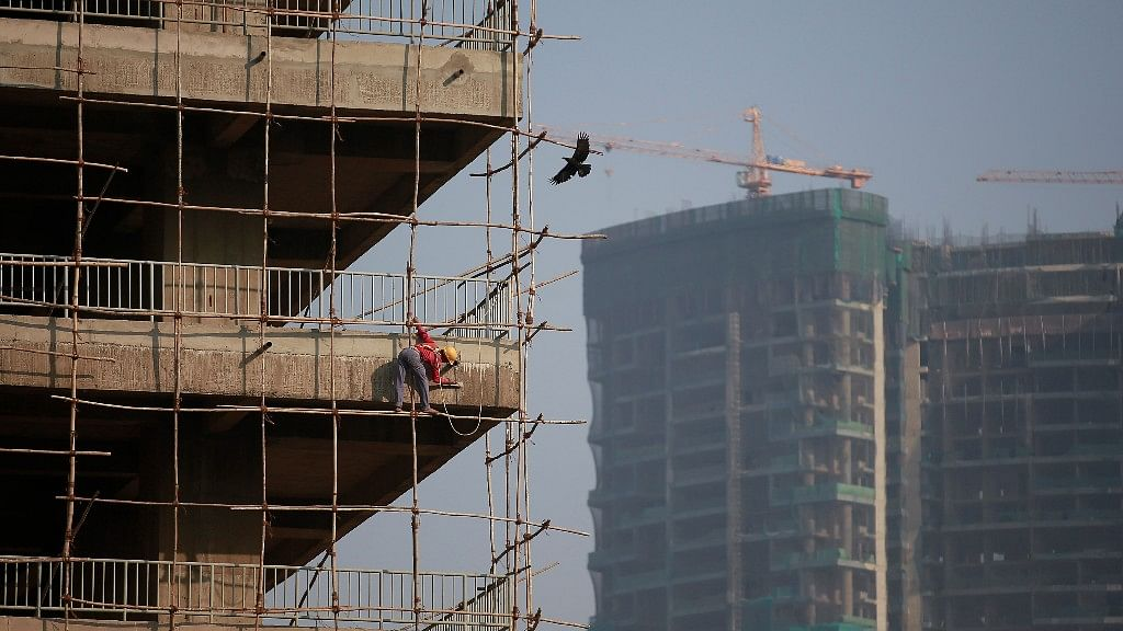 A labourer stands on wooden scaffolding as he works at the construction site of a commercial building in Mumbai's central financial district, 16 January 2015.