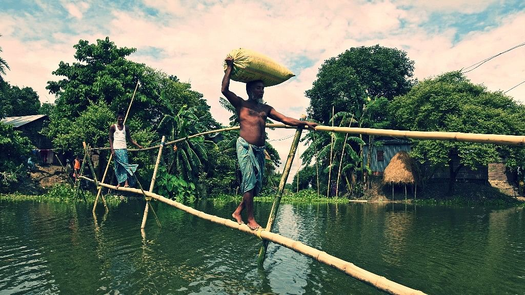 Villagers use a makeshift bamboo bridge to move across flooded areas of Morigaon district in the northeastern state of Assam.