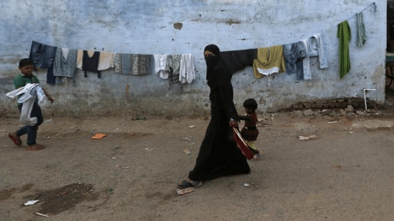 A Muslim woman and child walk through a locality of the Muslim dominated Johapura area in Ahmedabad.