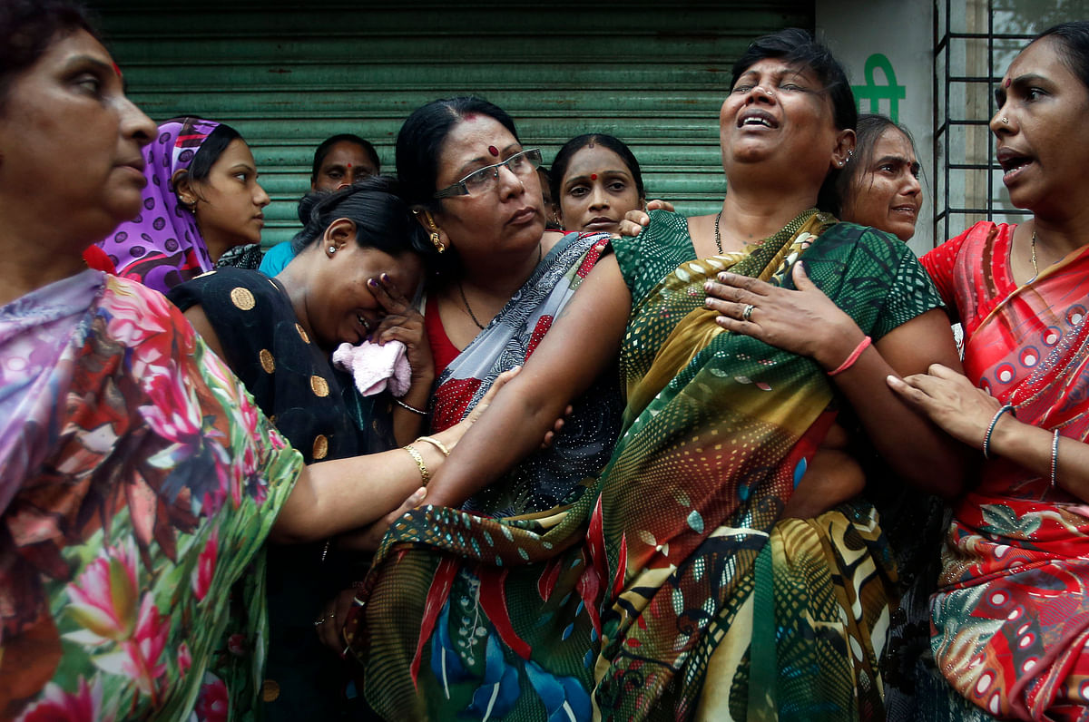 Relatives of residents trapped under the rubble react at the site of a collapsed residential building in Mumbai on 27 September 2013.
