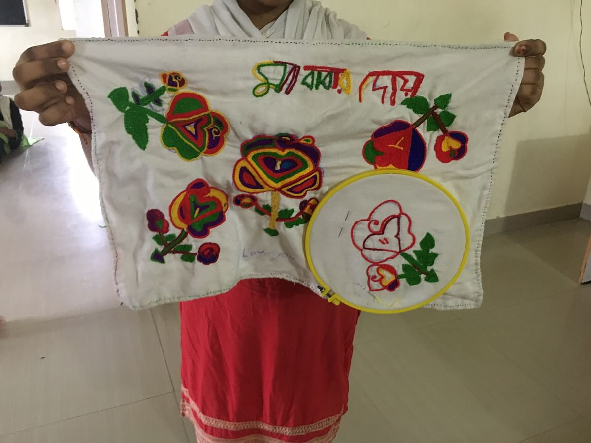 "A girl at a shelter house shows a cloth with embroidered Bengali words – ""Mother and father's kindness""."