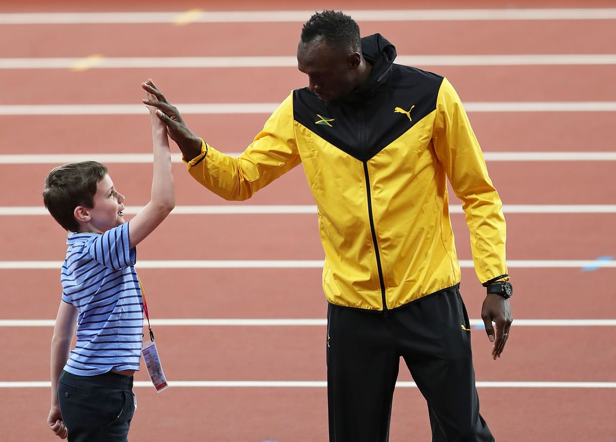 Usain Bolt greets a young boy during his lap of honour at the end of the World Athletics Championships in London on Sunday.