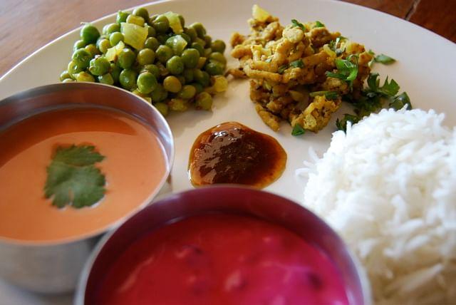 The marathi thali comprises santosh, beet raita, lemony green peas, tamarind chutney, ground chicken with cumin, and Basmati rice.
