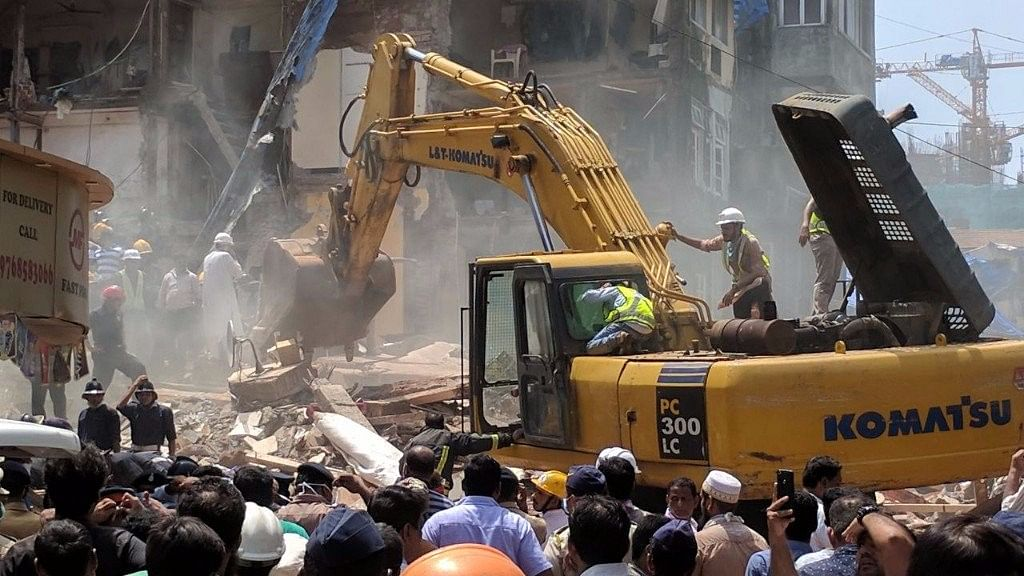 An excavator moves rubble aside as BMC and NDRF teams search for survivors at the collapse site.