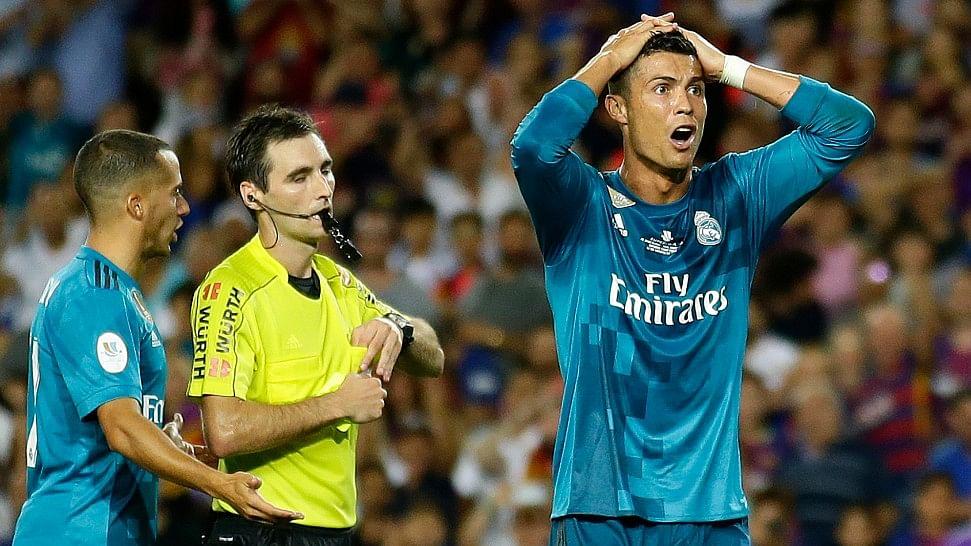 Real Madrid's Cristiano Ronaldo, right, reacts after Referee Ricardo de Burgos shows a yellow card.
