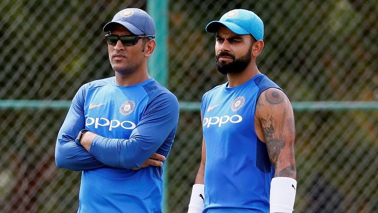MS Dhoni and Virat Kohli share a moment during a training session.