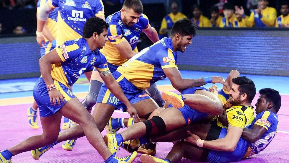 Telugu Titans and Tamil Thalaivas players in action.