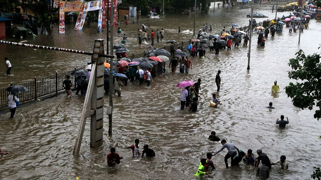 People walk through a waterlogged street following heavy rains in Mumbai.