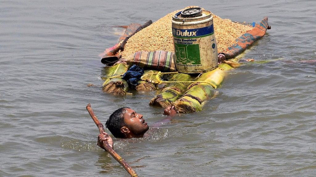 File image of a villager carries grains on a banana raft as he shifts from a flooded village in Araria district of Bihar.