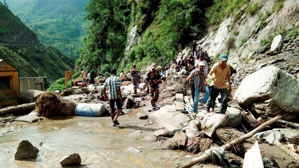 People walk towards a Kailash Mansarovar road after a cloud burst at Pithoragarh district in Uttarakhand on Monday.