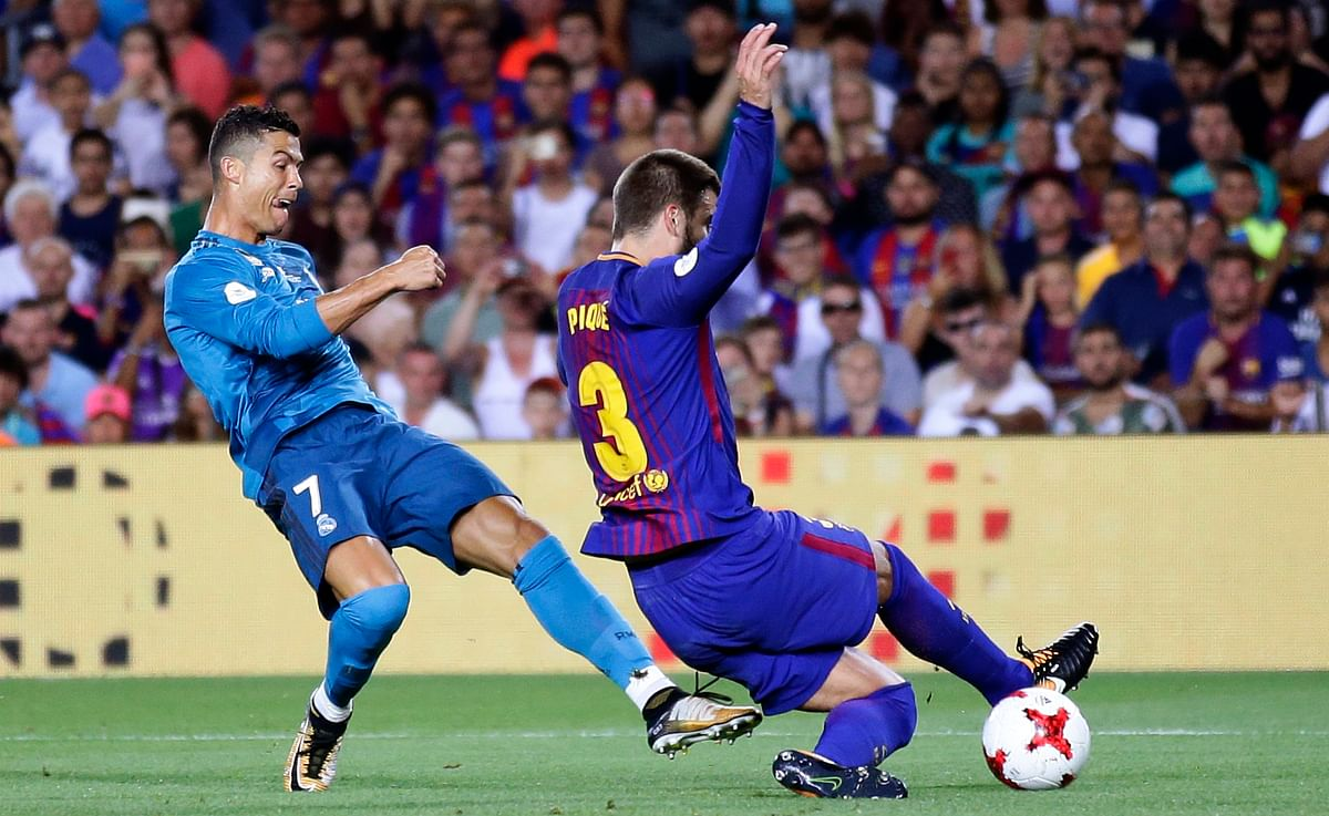 FC Barcelona's Gerard Pique, right, duels for the ball against Real Madrid's Cristiano Ronaldo.