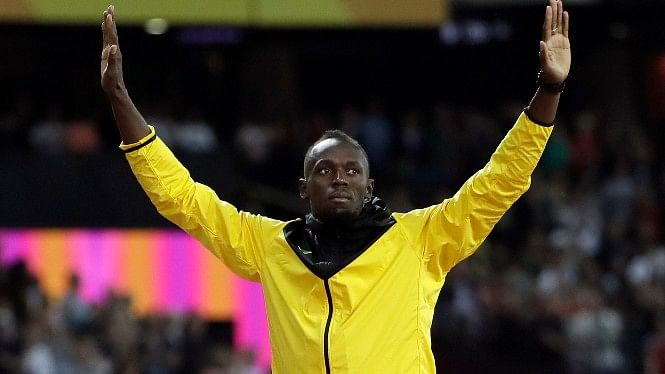 Usain Bolt waves as he walks away from the track after a lap of honour.