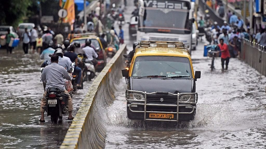 Vehicles plying at a waterlogged road after heavy rains in Mumbai.