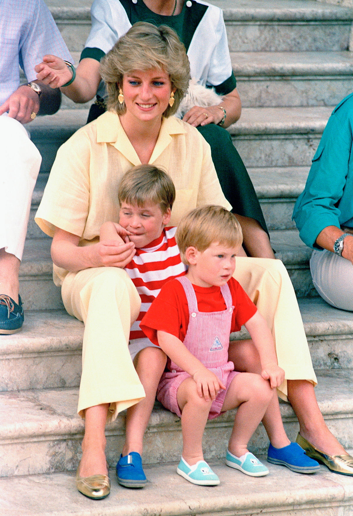 In this August 1987 photo, Britain's Princess Diana  smiles as she sits with her sons, Princes Harry (front) and William, on the steps of the Royal Palace on the island of Mallorca, Spain, where the British Royal family is on holiday with the Spanish King Juan Carlos and his family.