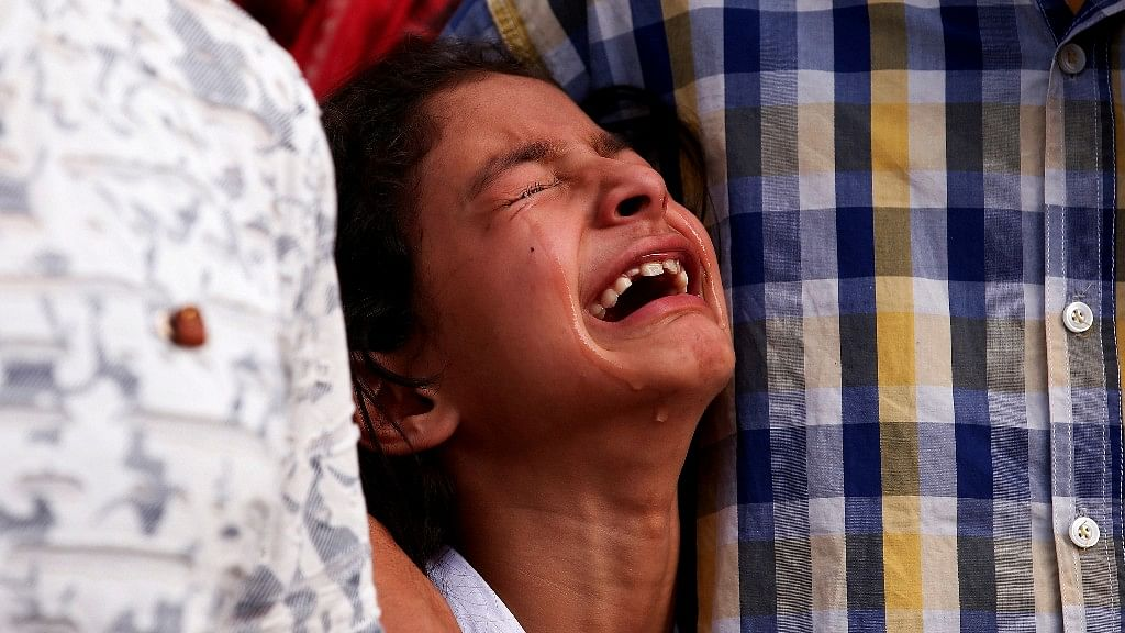 Zohra, the daughter of Abdul Rasheed mourns as policemen carry his body during his wreath laying ceremony in Srinagar, August 28, 2017.