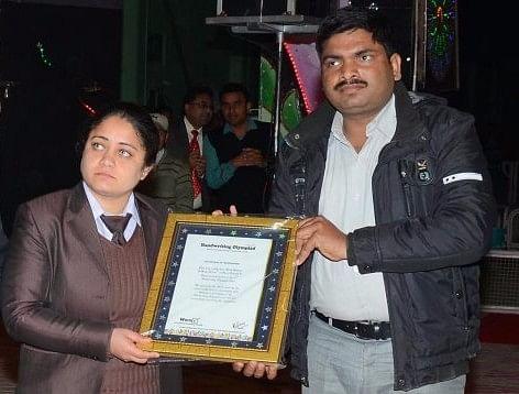 Vipasana  Insan handing  a certificate to a Dera member.