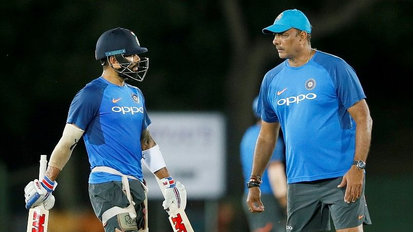India's captain Virat Kohli speaks to coach Ravi Shastri during a training session.