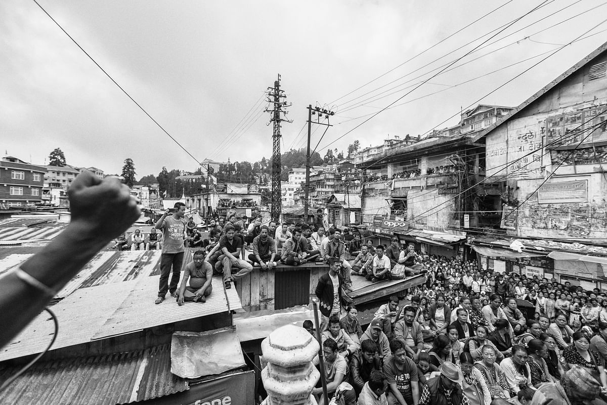 Locals listen to a leader during a rally conducted by Gorkha Janmukti Morcha (GJM), one of the major political parties from the hills, at Chowk Bazaar in Darjeeling.