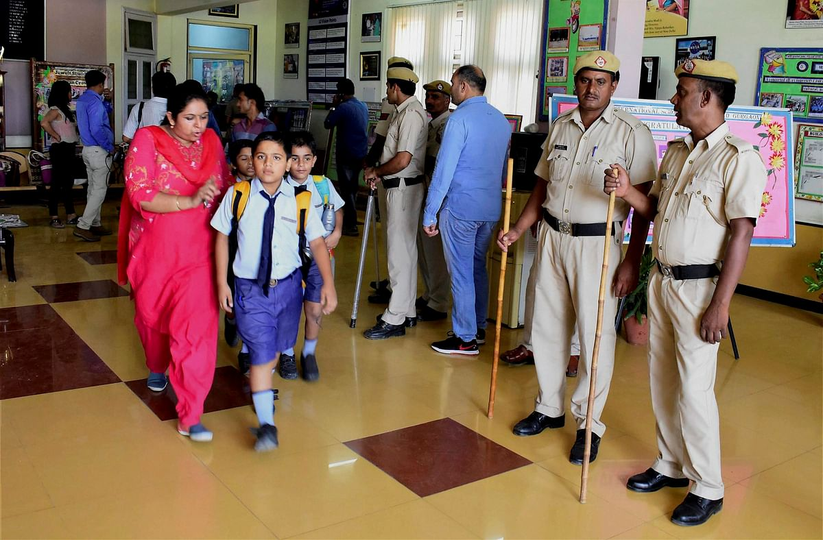 Parents take their children home after the murder of a class 2 student at Ryan International School as a police team looks on, in Gurugram on Friday.