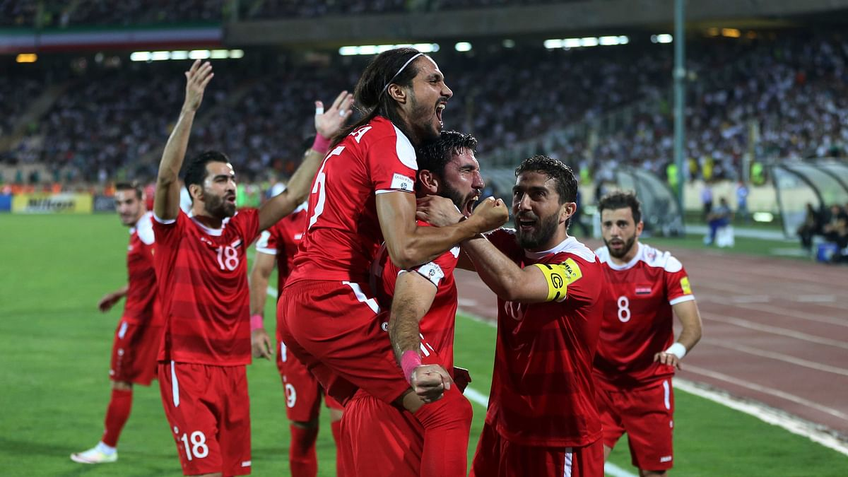 Syria's soccer team celebrates after scoring a goal against Iran during their Round 3 - Group A World Cup qualifier at the Azadi Stadium in Tehran.