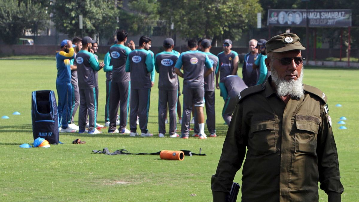 A Pakistani police officer stands guard while cricketers attend a training session for the upcoming World XI series at a ground in Lahore, Pakistan, Sunday, Sept. 10, 2017.