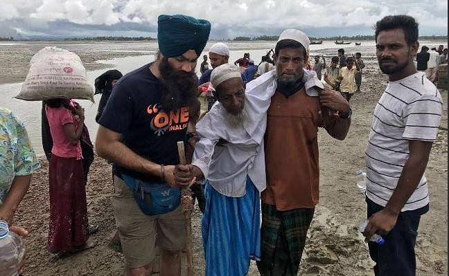 A Sikh volunteer from Khalsa Aid at Teknaf, on the Bangladesh-Myanmar border, helps Rohingya Muslims.