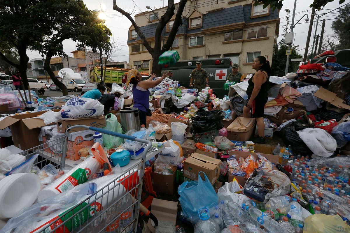 Volunteers organise donated supplies outside the Enrique Rebsamen school.