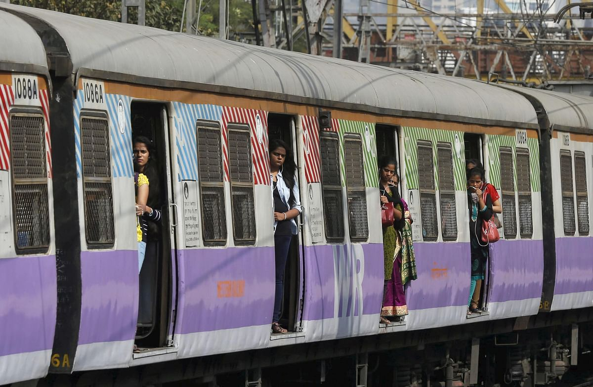 Commuters stand on the doors of a suburban train as it approaches the Churchgate railway station in Mumbai.