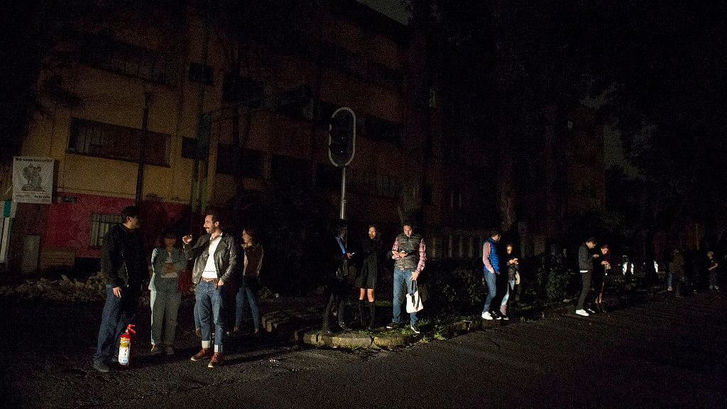 People stand in a  street in the La Roma neighbourhood of Mexico City after the earthquake.
