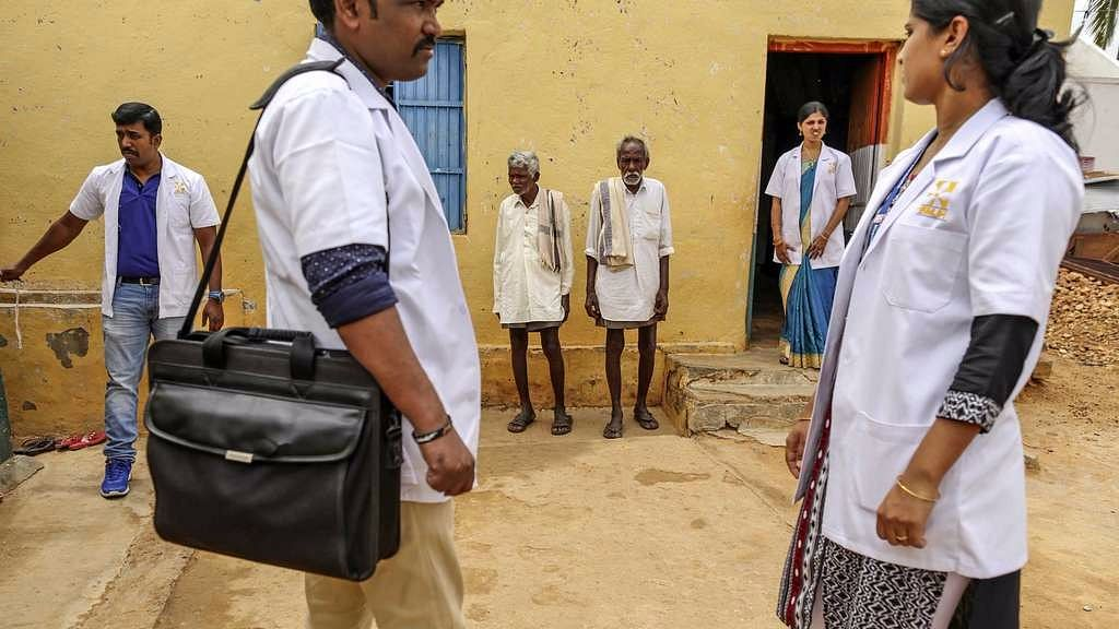 Villagers and medical staff stand outside a building in Pancharala, on the outskirts of Bengaluru, India, on 9 June 2017.
