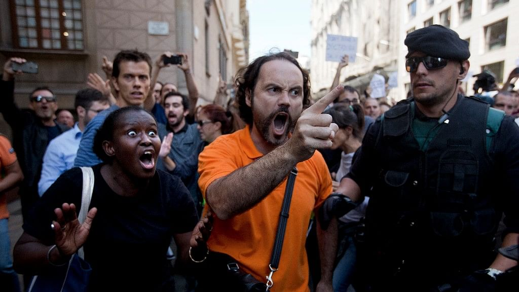 Demonstrators react as they try to stop the car carrying Xavier Puig, a senior at the Department of External Affairs, Institutional Relations and Transparency of the Catalan Government office, after he was arrested by Guardia Civil officers in Barcelona, Spain, on Wednesday.