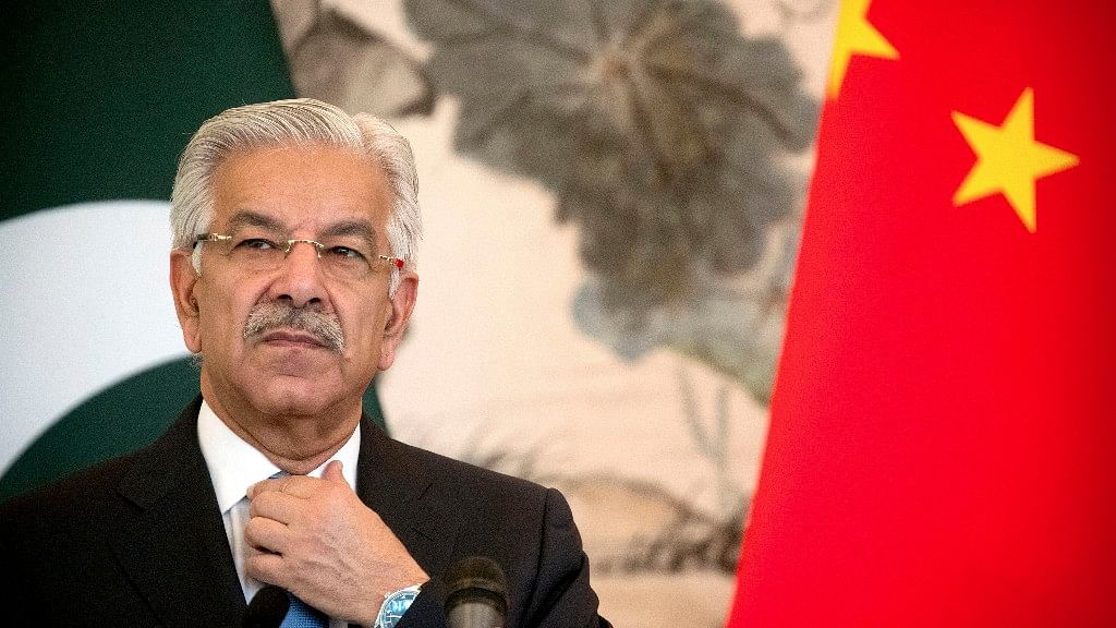 Pakistan's Foreign Minister Khawaja Muhammad Asif adjusts his necktie during a joint press conference at the Diaoyutai State Guesthouse in Beijing.