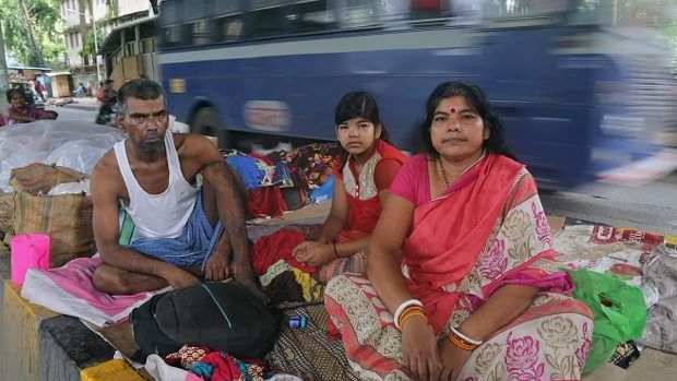 A cancer patient and his wife and daughter sit on the divider under the monorail station near Tata Memorial Hospital, Parel, Mumbai. Unable to afford a hotel or a dharmshala (rest house), many live on the pavements till treatment is complete.