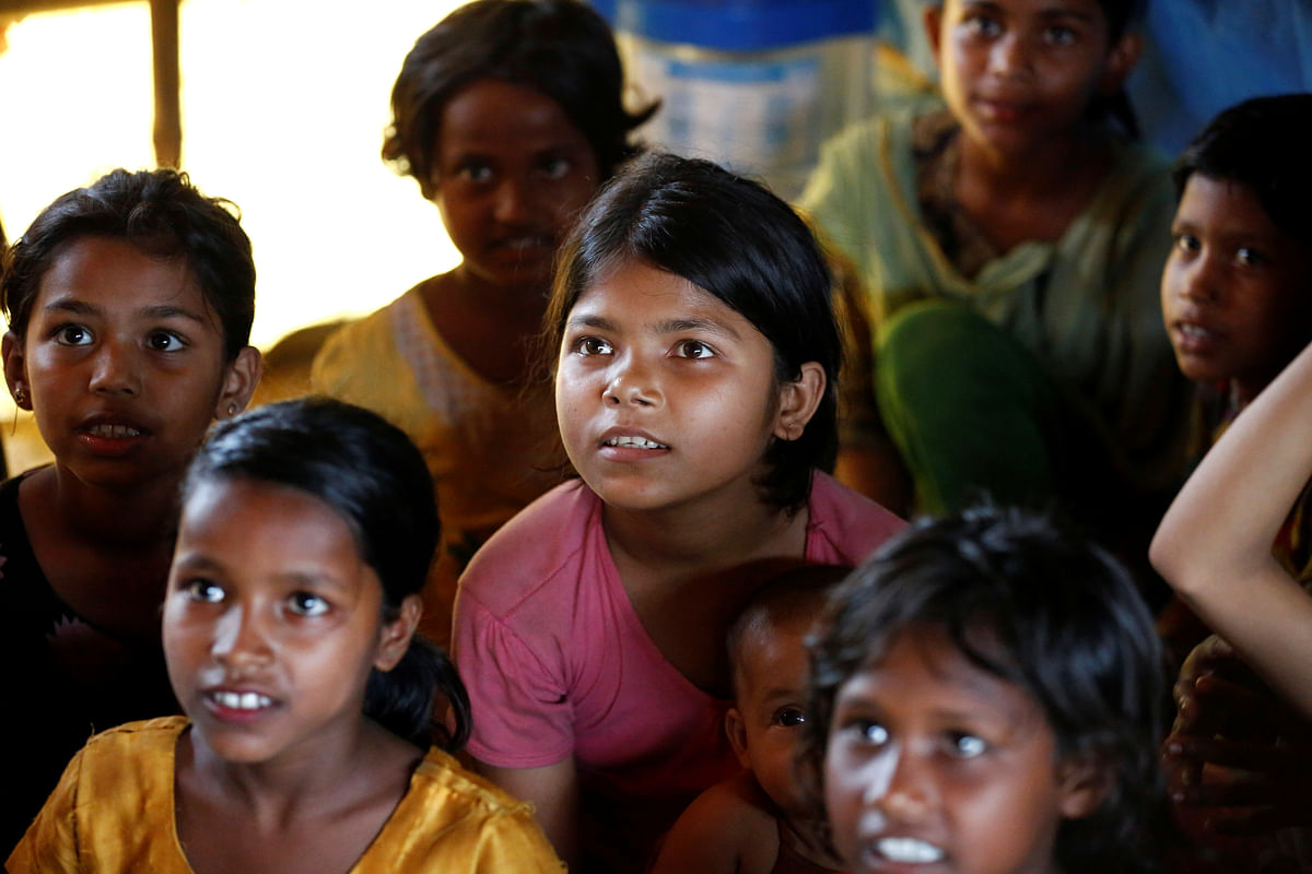 Rohingya refugee children pay attention to the teacher as they attend a session in a makeshift school at Balukhali Makeshift Refugee Camp in Cox's Bazar, Bangladesh.