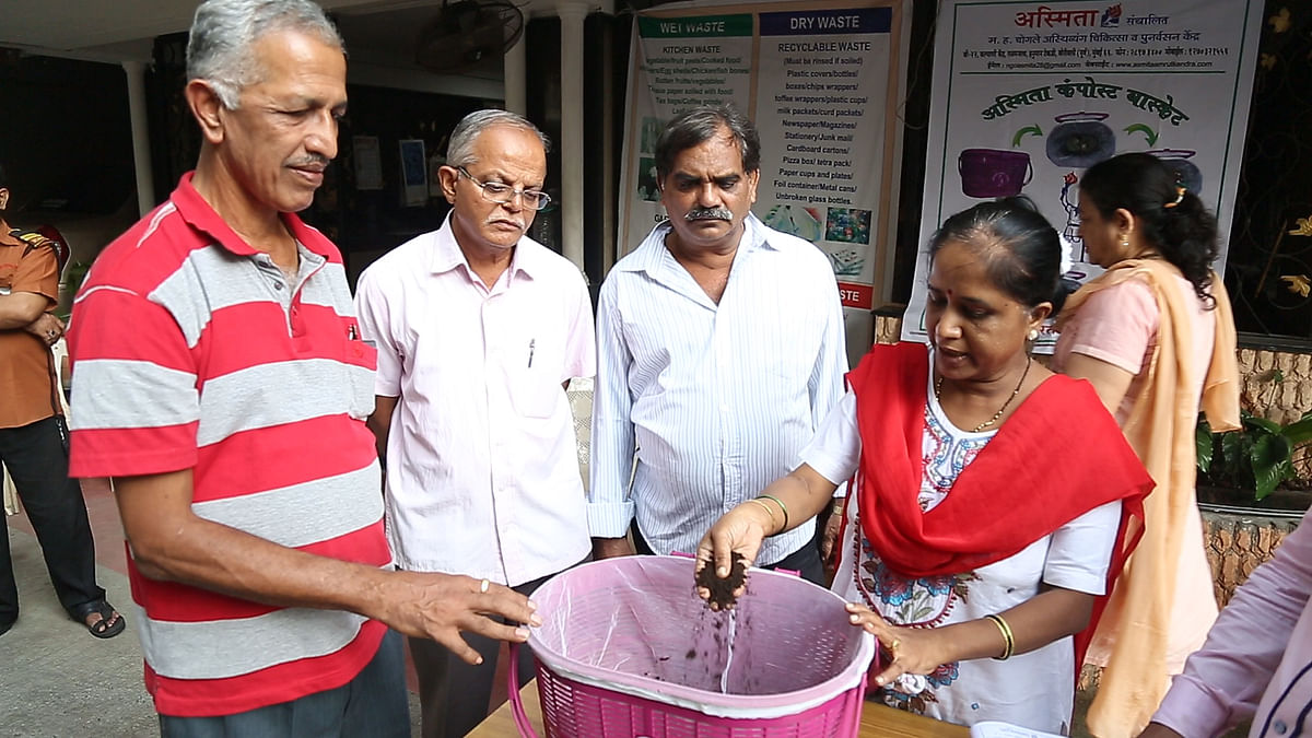 A volunteer from Asmita NGO demonstrates the technique of using compost basket to residents.