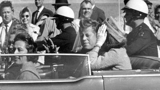 President John F Kennedy waves from his car in a motorcade approximately one minute before he was shot in Dallas.