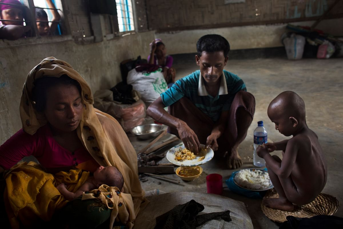 In this Thursday, 7 September 2017 photo, 25-year-old Rohingya Muslim woman Zahida Begum cradles her few-hours-old son who she gave birth to alone in the toilet outside the room, as her husband Abdur Rahman mixes a plate of rice for his wife at Kutupalong refugee camp, Bangladesh.