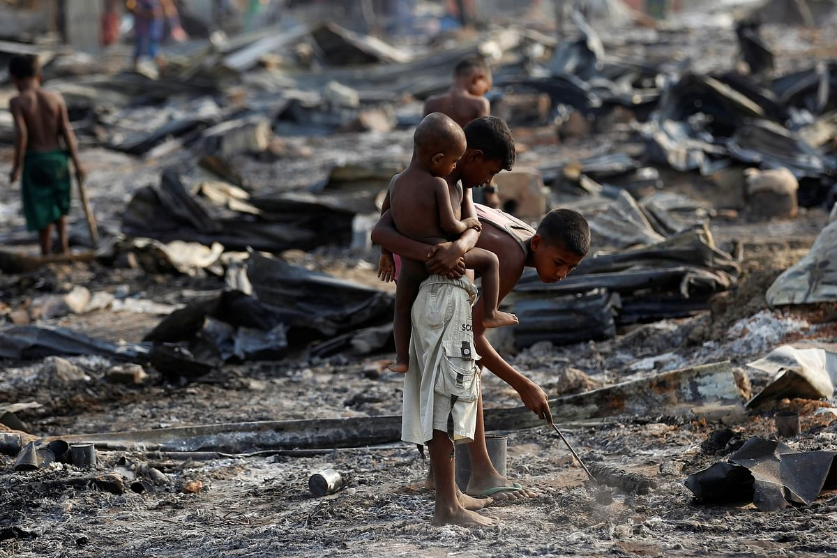 Boys search for useful items among the ashes of burnt houses after fire destroyed shelters at a camp for internally displaced Rohingya Muslims in the western Rakhine State near Sittwe, Myanmar