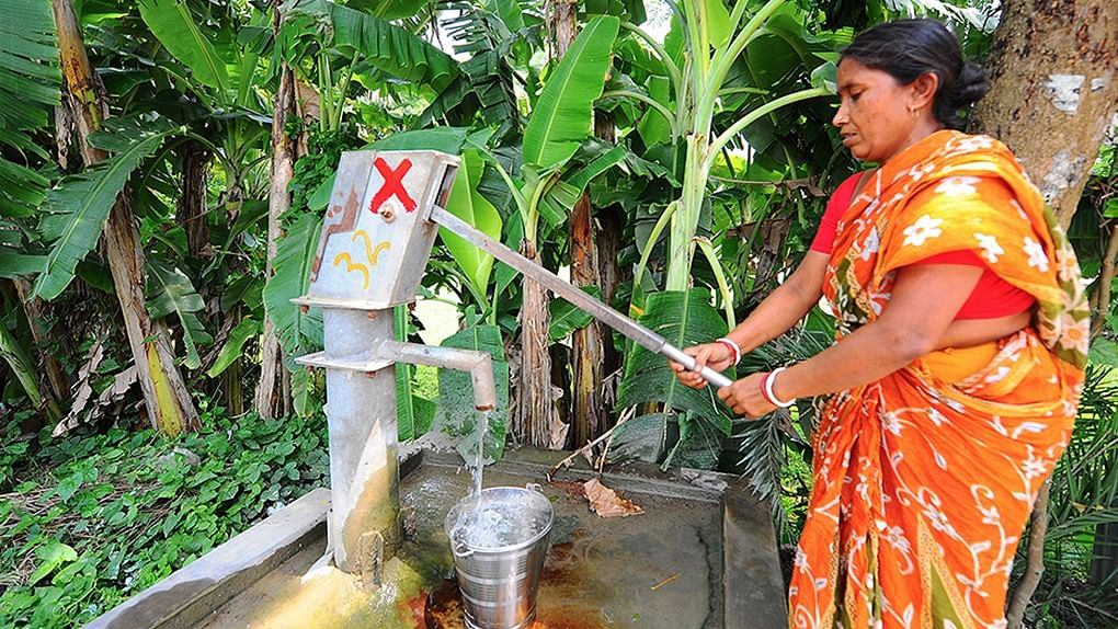 A woman pumps up water from a tubewell in West Bengal despite the red cross that signifies that there is an unacceptable level of arsenic in the water.