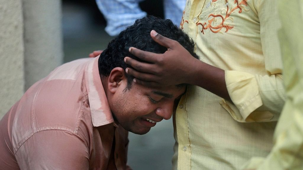 A man mourns outside a morgue for a relative killed in the Elphinstone bridge stampede.