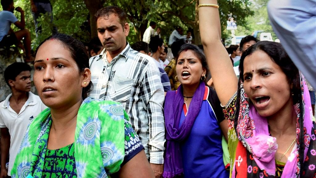 Demonstrators raise slogans during a protest outside Ryan International School as they demand action against the school.